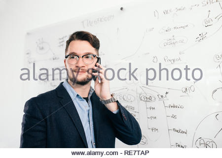 Close-up portrait of young  dark-haired man standing near whiteboard and talking on phone in office. He wears blue shirt, dark jacket, glasses. He smiles to the side. - Stock Photo