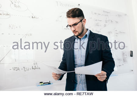 Portrait of young attractive dark-haired guy in glasses checking documents in office. He stands near white desk with planning. He wears blue shirt with jacket. - Stock Photo