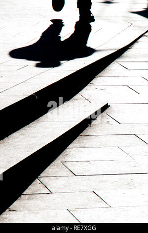 Blurry silhouette shadow of a man walking on a city sidewalk with steps  in black and white high contrast - Stock Photo