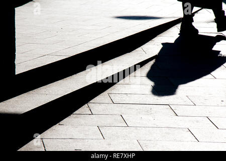 Blurry silhouette shadow of a person walking on a city sidewalk in winter in black and white high contrast - Stock Photo
