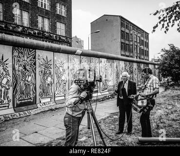 August 1986, CBS TV crew conducting an interview in front of Berlin Wall decorated with Statue of Liberty frescos, West Berlin side, Germany, Europe, - Stock Photo