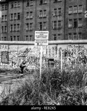 August 1986, Berlin Wall graffitis, warning sign for end of American sector, cyclist, East Berlin building, West Berlin side, Germany, Europe, - Stock Photo