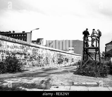 August 1986, Berlin Wall graffitis, people on observation platform looking over the Wall, Zimmerstrasse street, West Berlin side, Germany, Europe, - Stock Photo