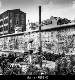 August 1986, young woman with bike, Peter Fechter memorial, graffitis on Berlin Wall, Zimmerstrasse street, Kreuzberg, West Berlin, Germany, Europe, - Stock Photo