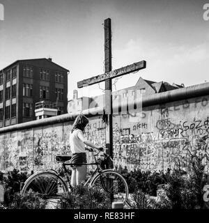 August 1986, young woman with bike, Peter Fechter memorial, graffitis on Berlin Wall, Zimmerstrasse street, Kreuzberg, West Berlin, Germany, Europe, - Stock Photo