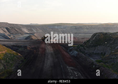 Giant size water tank truck driving on a road inside a large open pit coal mine in the Powder River Basin of Wyoming. - Stock Photo
