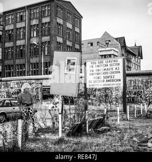 August 1986, woman and boy, leaving American sector warning sign, Berlin Wall graffitis, Zimmerstrasse street, West Berlin side, Germany, Europe, - Stock Photo