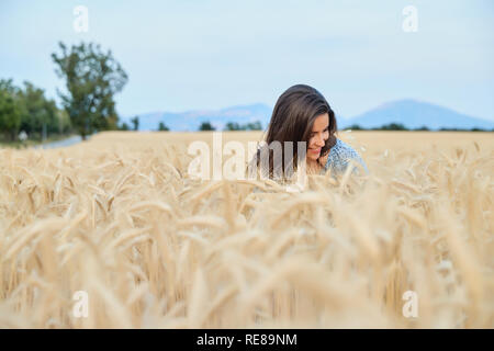 The beautiful young girl with long brunette hairs poses in the field with wheat, sunset light, turns, smiles, flirts,  happy, blue dress, France, Prov - Stock Photo