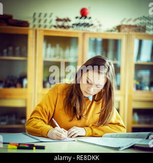 Young female college student in chemistry class, writing notes. Focused student in classroom. Authentic Education concept. - Stock Photo