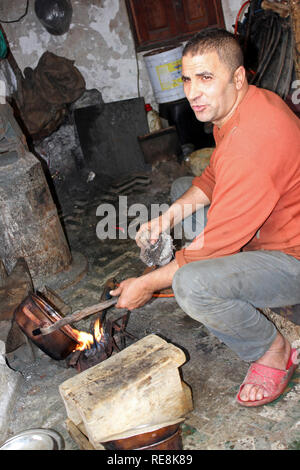 Metalworker in his workshop at the Place el Seffarine, Medina of Fes el Bali, Fez, Morocco - Stock Photo