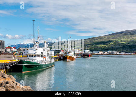 Akureyri, Iceland - June 17, 2018: Fishing village town harbor marina with boats and ships reflection of sky in blue green calm water and mountain lan - Stock Photo