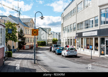 Akureyri, Iceland - June 17, 2018: Empty street road alley in town village city with car by restaurant signs in summer morning day - Stock Photo