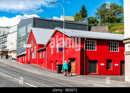 Akureyri, Iceland - June 17, 2018: Street road in town village city with colorful vibrant red painted house restaurant and people walking on sidewalk  - Stock Photo
