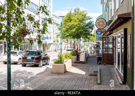 Akureyri, Iceland - June 17, 2018: Street road in town village city with sidewalk and signs forrestaurants stores shops with cars in traffic - Stock Photo