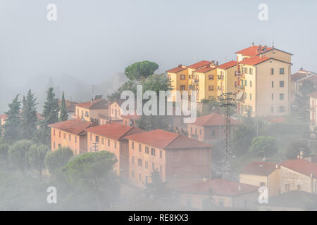 Chiusi Scalo mist fog sunrise of rooftop houses buildings in Umbria, Italy near Tuscany with soft clouds haze covering blanketing town cityscape skyli - Stock Photo
