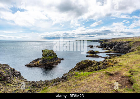 Landscape view rocks in ocean on coast in Hellnar National park Snaefellsnes Peninsula coastline in Iceland with green grass on summer day - Stock Photo