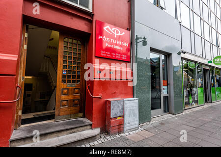 Reykjavik, Iceland - June 19, 2018: Street road sidewalk in downtown center and sign for post office with colorful red building door entrance and nobo - Stock Photo