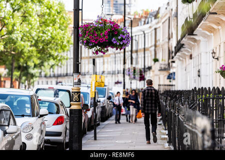 London, UK - June 21, 2018: Neighborhood district of Victoria of Pimlico with terraced housing buildings and hanging flower baskets in old vintage his - Stock Photo