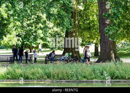 London, UK - June 21, 2018: St James Park green trees in sunny summer with many people walking on sidewalk by pond river water and sitting on benches - Stock Photo