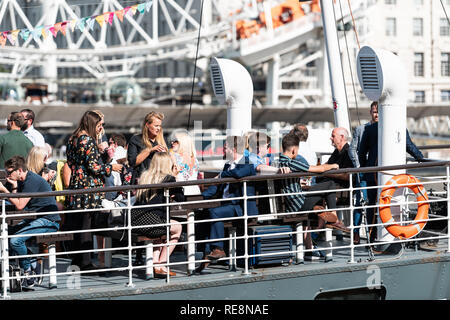 London, UK - June 21, 2018: Many people tourists sitting in boat ship on Thames River looking at view of London Eye in restaurant cafe pub - Stock Photo