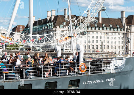 London, UK - June 21, 2018: Many people tourists sitting in boat ship pub called Tattershall Castle on Thames River looking at view of London Eye in r - Stock Photo