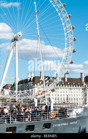London, UK - June 21, 2018: Many people tourists sitting in boat ship pub called Tattershall Castle on Thames River looking at London Eye in restauran - Stock Photo