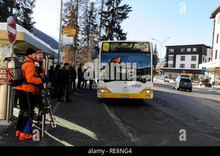 Skiers waiting at the local bus stop  in the Promenade, Davos. Switzerland - Stock Photo