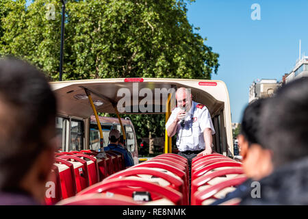 London, UK - June 22, 2018: Top of Big Bus double decker with guided tour guide speaking on microphone and tourists sitting in seats - Stock Photo