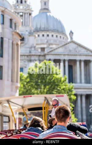 London, UK - June 22, 2018: Top of Big Bus double decker with guided tour guide and tourists sitting in seats with vertical view of St Paul's Cathedra - Stock Photo