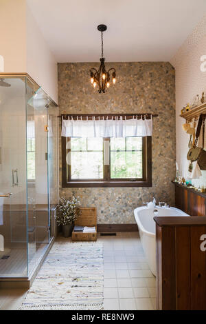 Glass shower stall and antique style freestanding roll top bathtub in En suite on upstairs floor inside  LEED certified Country home - Stock Photo