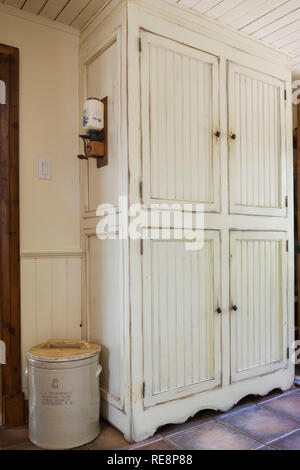 Floor to ceiling cream coloured antique finish wooden armoire in kitchen inside an old 1892 Canadiana cottage style home - Stock Photo