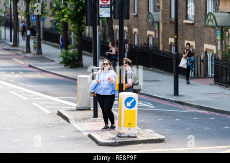 London, UK - June 22, 2018: High angle view of street with people standing waiting to cross road in city - Stock Photo
