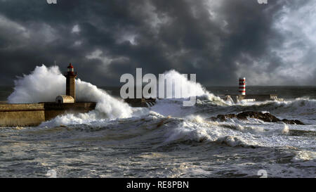 Stormy sunset at the harbor of the mouth of the river Douro, in Porto, Portugal, with big waves against old lightouse, new pier and beacon; enhanced s - Stock Photo