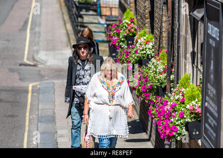 London, UK - June 22, 2018: Two people older senior old couple in stylish fashion summer clothers walking on sidewalk street road during sunny summer  - Stock Photo