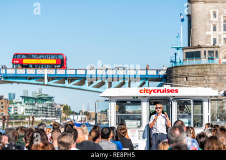 London, UK - June 22, 2018: Tour guide and many tourists sitting in boat cruise ship tour on Thames River looking at view of city tower bridge and red - Stock Photo