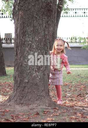 happy little girl playing hide and seek in the city Park
