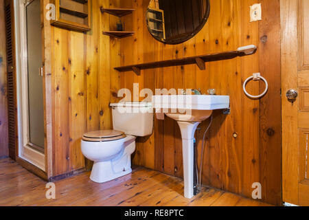 White pedestal sink, toilet and glass door shower stall in bathroom with planked wood floor, ceiling and walls inside an old 1807 Canadiana style home - Stock Photo