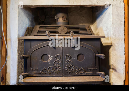 Black cast iron Acorn Voyageur wood burning stove installed in fireplace inside an old 1807 Canadiana style home - Stock Photo