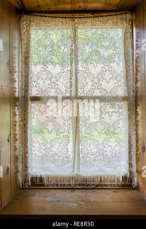 Recessed window with white lace curtains inside an old 1807 Canadiana style home - Stock Photo