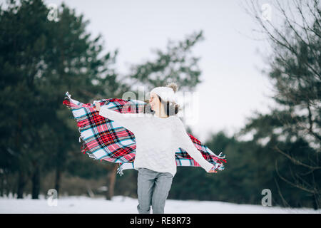 Young woman runs and laughs with scarf in her hands in the winter pine forest. Stock Photo