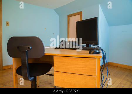 Modern office sitting chair and wooden desk with computer in blue bedroom home office on upstairs floor inside an old 1807 Canadiana style home - Stock Photo