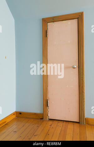 Old wooden closet door covered with rose coloured wallpaper in blue bedroom on upstairs floor inside an old 1807 Canadiana style home - Stock Photo