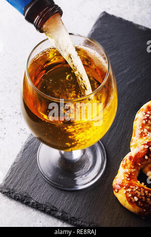 Process of pouring light beer in a glass - Stock Photo