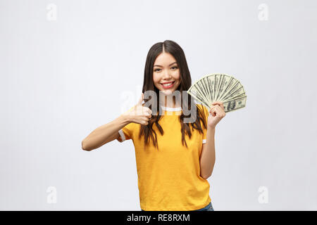 Closeup portrait of beautiful asian woman holding money isolated on white background. Asian girl counting her salary dollar note. Success wealth financial business cashflow currency payment concept - Stock Photo