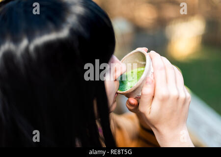 Woman holding tea cup face closeup drinking outside in backyard garden with girl and green matcha black hair