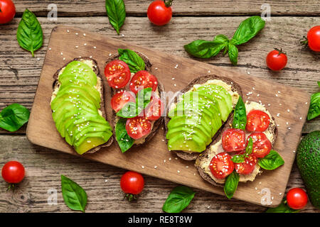 Breakfast sandwiches with avocado, tomatoes, basil, hummus and sesame seeds on rustic cutting board. Healthy snack. top view - Stock Photo