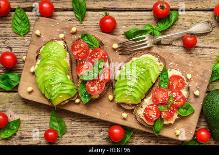 vegan sandwiches with avocado, tomatoes, basil, hummus and sesame seeds on rustic cutting board with fork. Healthy snack for breakfast. top view - Stock Photo