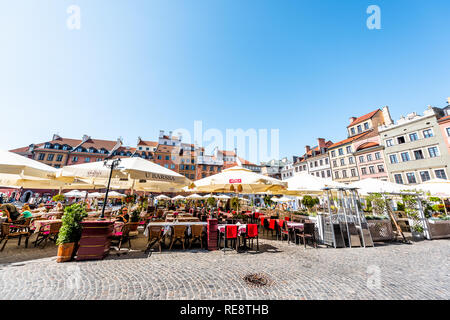 Warsaw, Poland - August 22, 2018: Tables outside Barssa restaurant with Polish food in old town market square with historic cobblestone street during  - Stock Photo