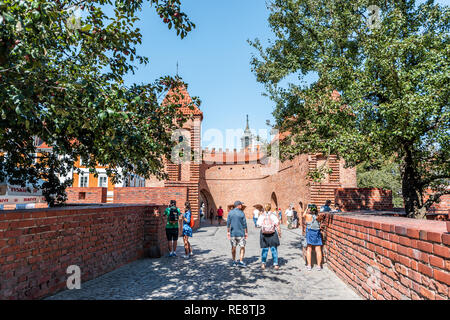 Warsaw, Poland - August 22, 2018: Famous old town historic street in capital city during sunny summer day and red orange brick wall fortress people wa - Stock Photo