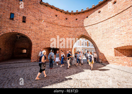 Warsaw, Poland - August 22, 2018: Famous old town historic street in capital city during summer day and red orange brick wall fortress people walking - Stock Photo